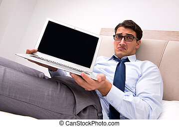 Businessman working in the bed at home