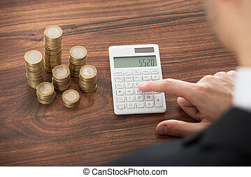 Businessman Working On Calculator