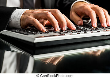Businessman working on computer by typewriting