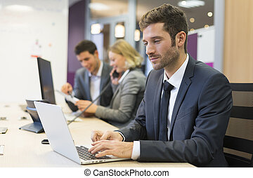Businessman working on computer in modern office, colleagues in background