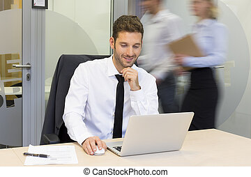 Businessman working on computer in office, business people moving behind him