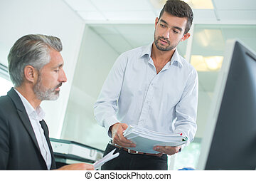 businessman working on computer with coworker in office