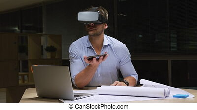 Businessman working on laptop and using VR helmet in a modern office