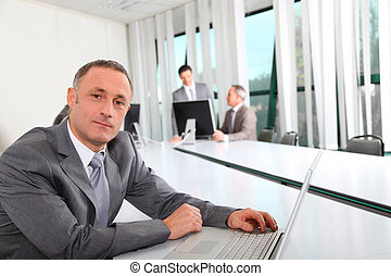 Businessman working on laptop computer in office