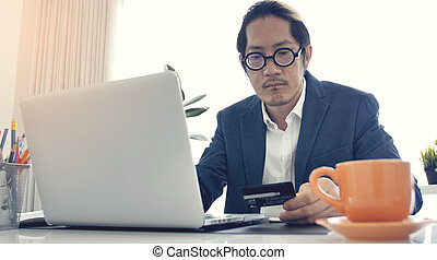 Businessman working on laptop computer with credit card.