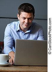 Businessman Working On Laptop In Internet Cafe