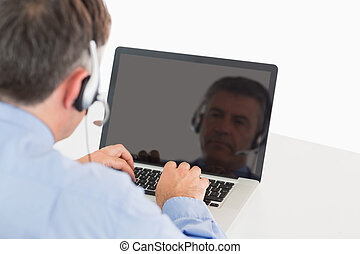 Businessman working on laptop with headset