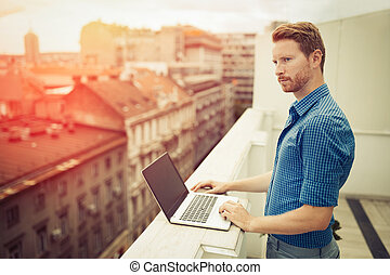 Businessman working on rooftop terrace