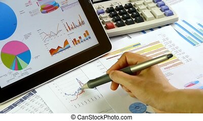 Businessman working on tablet with diagrams, calculation of financial data.