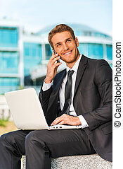 Businessman working outdoors. Handsome young man in formalwear working on laptop and talking on the mobile phone while sitting outdoors and against building structure