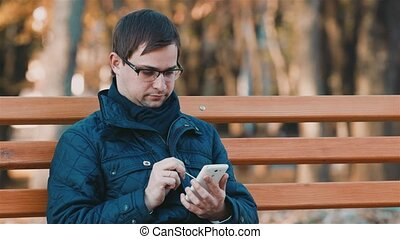 Businessman working with a smartphone in the autumn park