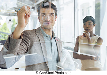 Businessman working with businesswoman and writing on transparent board