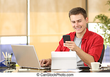Happy businessman working online with multiple devices and holding a smart phone in a desk at office