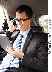 businessman working with tablet and smart phone in the car