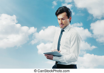 Businessman working with touchpad blue sky