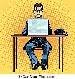 Businessman works behind laptop