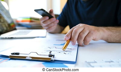 Businessman works with a smartphone and analyzes charts
