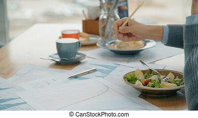 Businessman writes on blueprint, talks on phone, dines at...