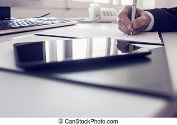 Businessman writing at a desk in a low angle view