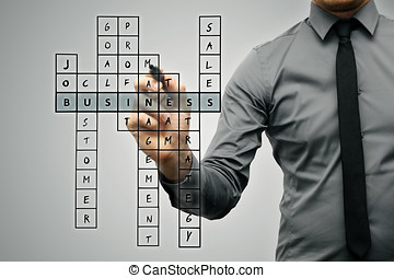 businessman writing business concept by crossword