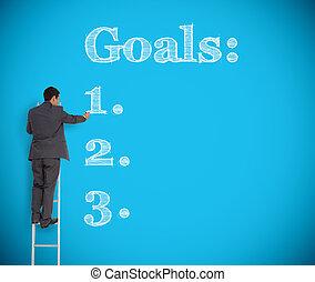 Businessman writing goals on a gian