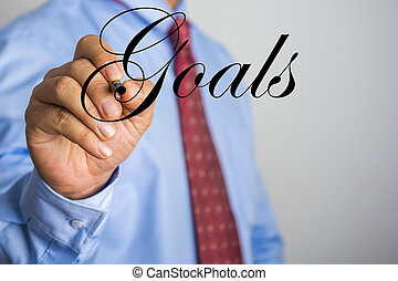 Businessman writing Goals word on virtual screen