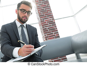 Businessman writing in a notebook in an office