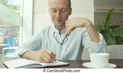 Businessman writing in the daily planner, diary and wear...