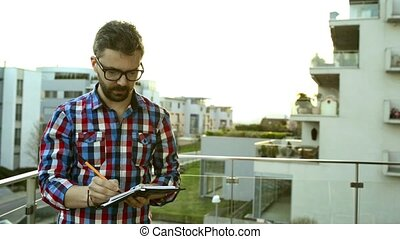 Businessman writing into his personal organizer standing on balcony
