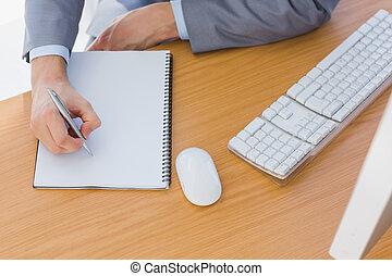 Businessman writing on blank notepad