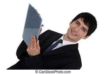Businessman writing on clip-board