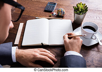 Businessman Writing On Notebook With Pencil