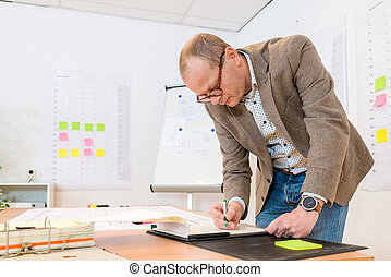 Businessman Writing On Notepad At Desk