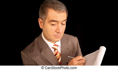 Businessman writing on notepad
