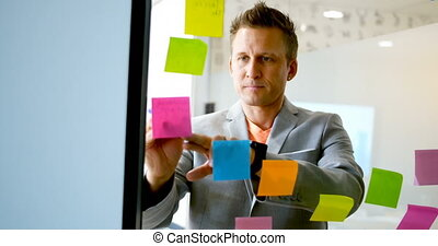 Businessman writing on sticky note on glass wall 4k -...