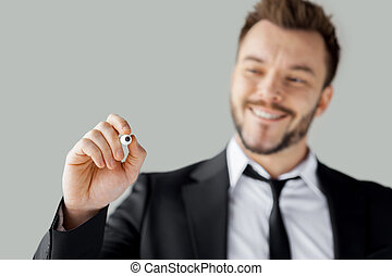 Businessman writing on transparent wipe board. Cheerful young man in formalwear writing something on transparent wipe board while standing against grey background