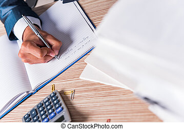 Businessman writing report in the office
