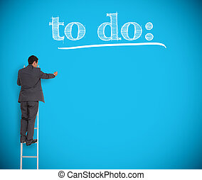 Businessman writing to do list on a blue wall
