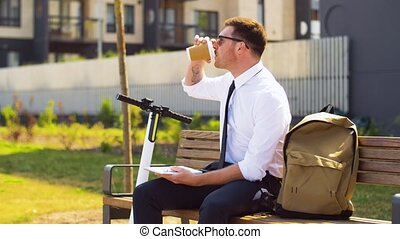 businessman writing to notepad and drinking coffee -...