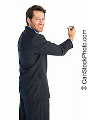 Businessman writing with marker while looking at camera
