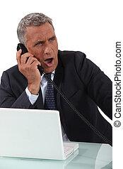Businessman yawning on the phone