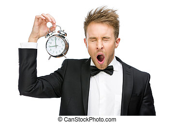 Half-length portrait of yawning businessman keeping alarm clock, isolated on white