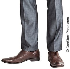 Businessmans feet in brown brogues on white background
