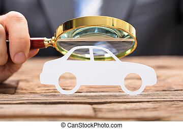 Businessman's Hand Examining Paper Car With Magnifying Glass