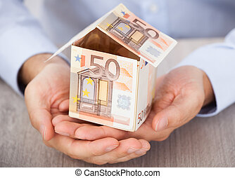 Businessman's Hand Holding House Made Of Euro Notes