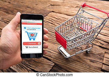 Businessman's Hand Holding Smartphone By Shopping Cart On Table