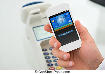 Businessman's Hand Paying Through Mobilephone