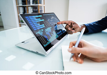 Businessman's Hand Pointing Laptop Screen Showing Bar Graph