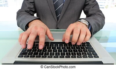 Businessmans hands typing on laptop