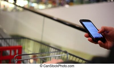 Businessmans hands using phone in the shopping mall until go escalator with trolley. Close up.